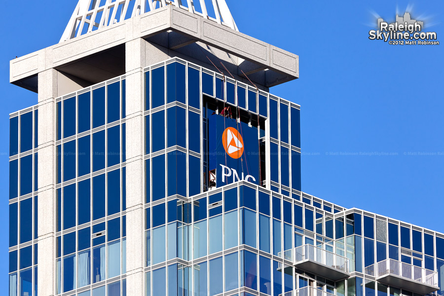 Men work to install the PNC Bank sign on the former RBC Plaza