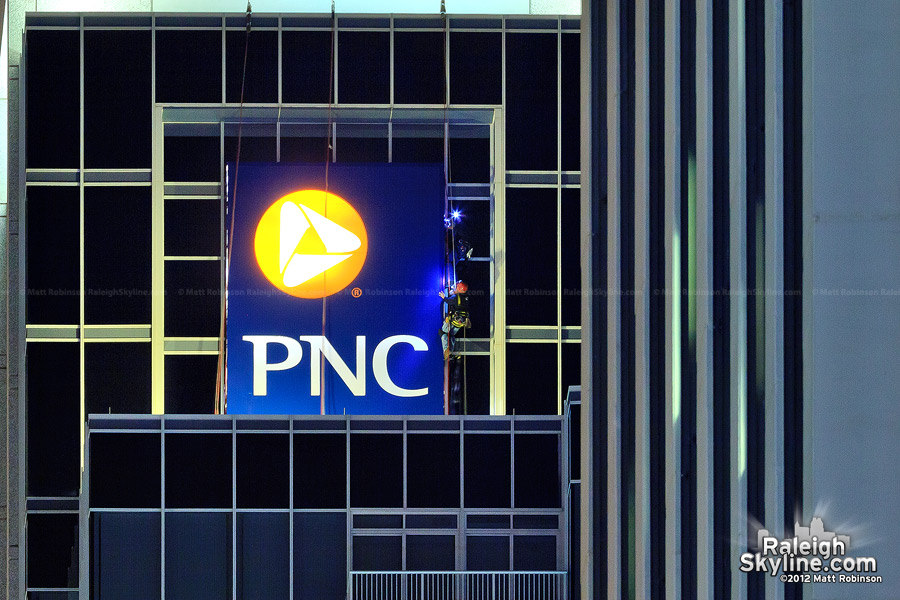 Workers on Raleigh's PNC Bank sign at night