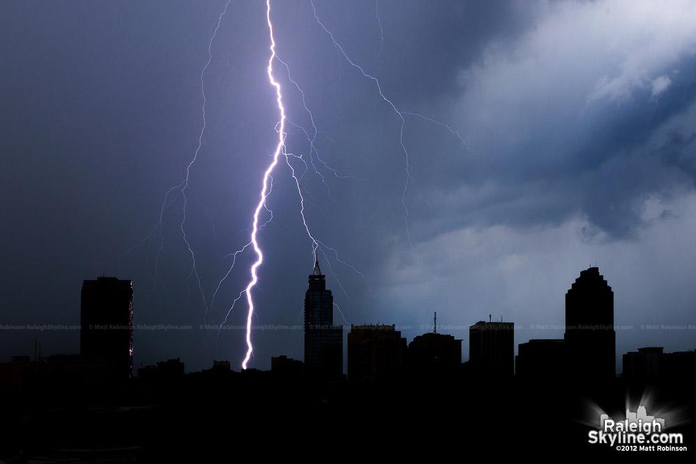 Daytime lightning strike silhouettes Raleigh from Boylan Avenue