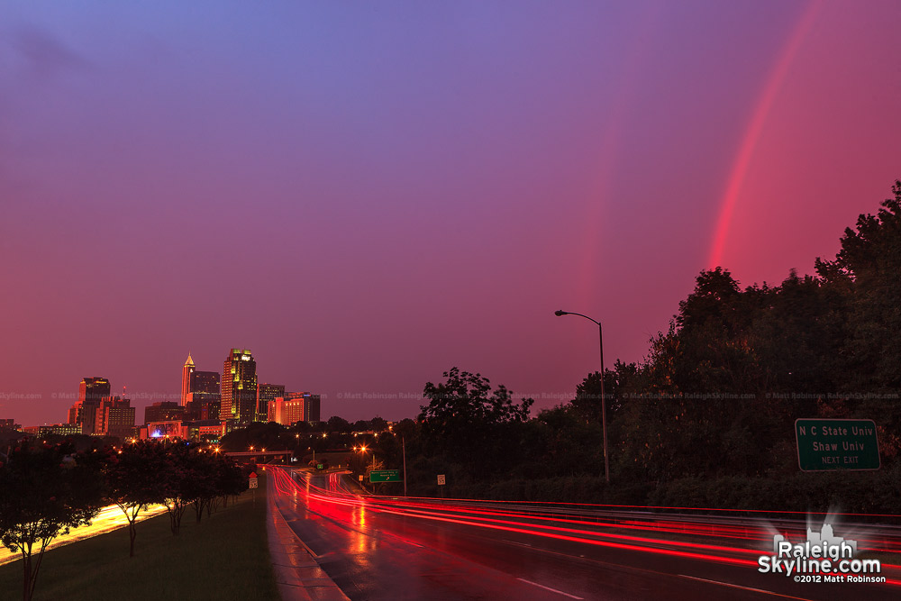 Surreal scene over Raleigh with rainbow and setting sun after a storm