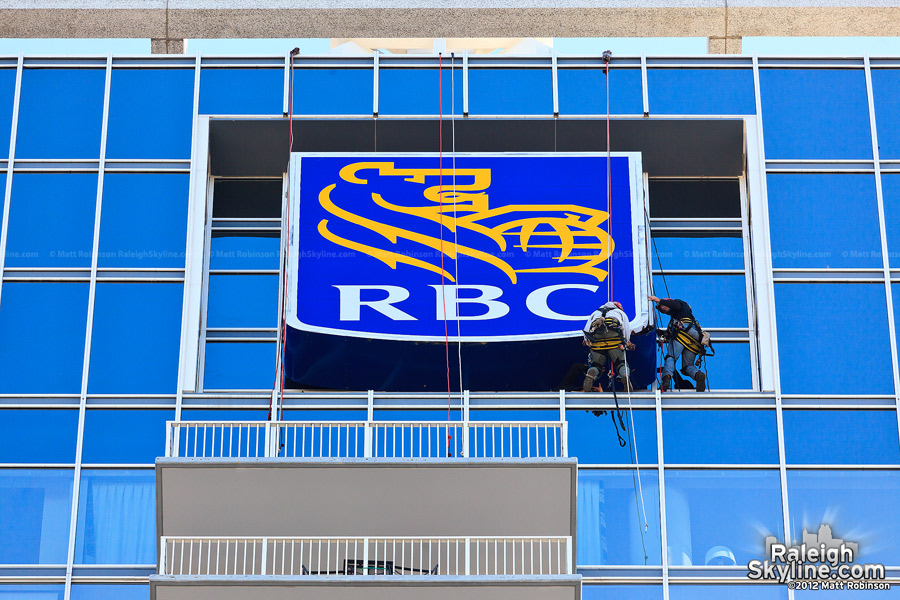 Two workers rappel to replace the RBC Plaza's sign