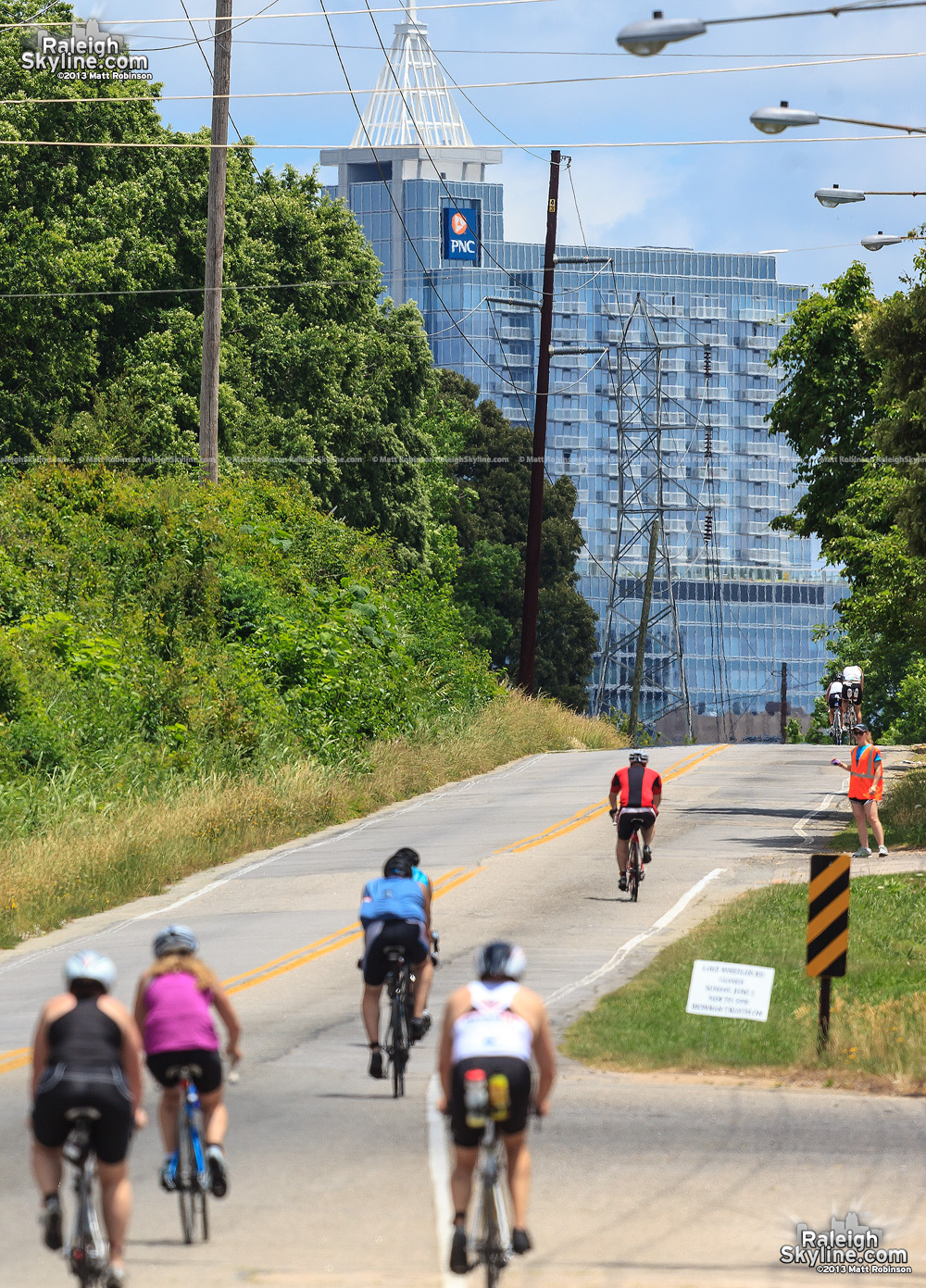 Raleigh Ironman cyclists ride up Lake Wheeler Road toward downtown Raleigh with PNC Plaza