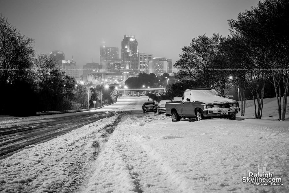 Black and White abandoned cars in the snow with Raleigh skyline