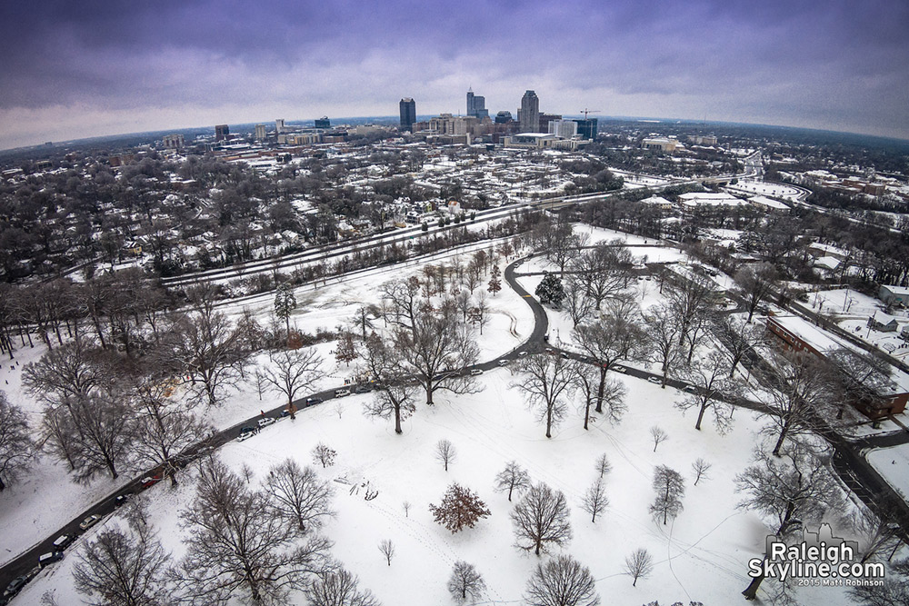 Aerial of sledding at Dorothea Dix with downtown Raleigh