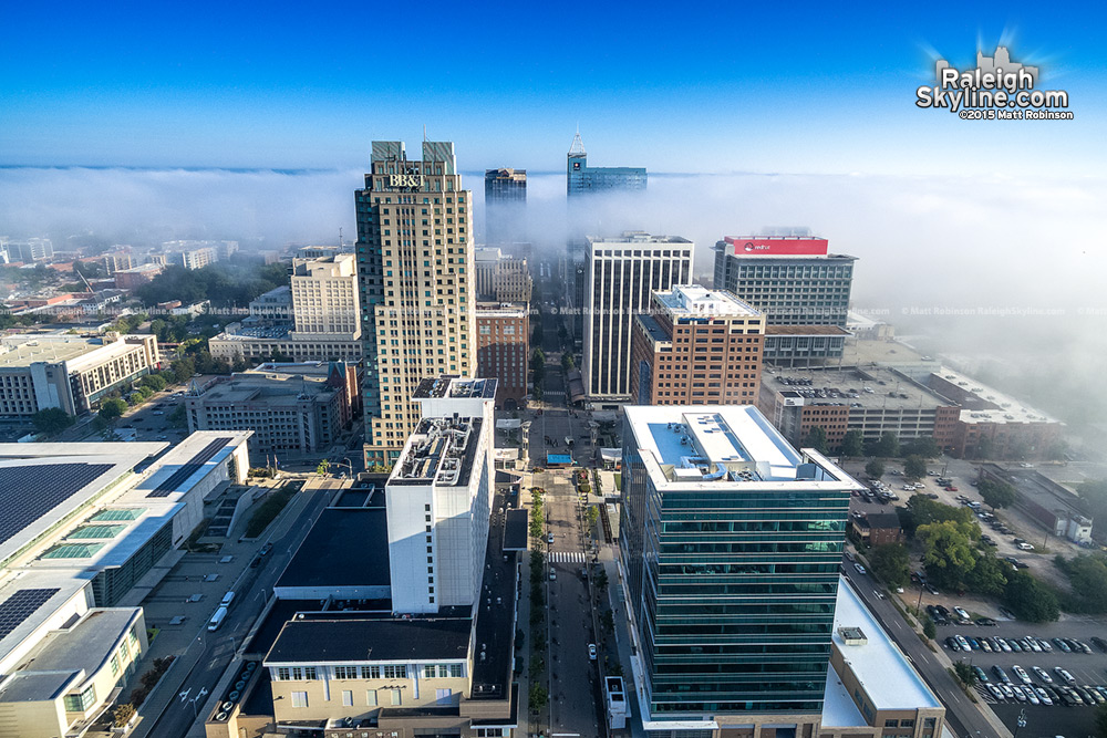 Fog ebbs between Raleigh Buildings