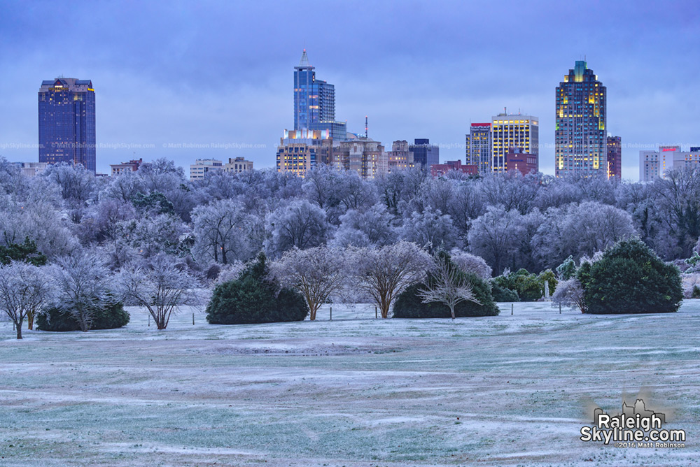 Raleigh rises over icy trees after the snowstorm at dusk