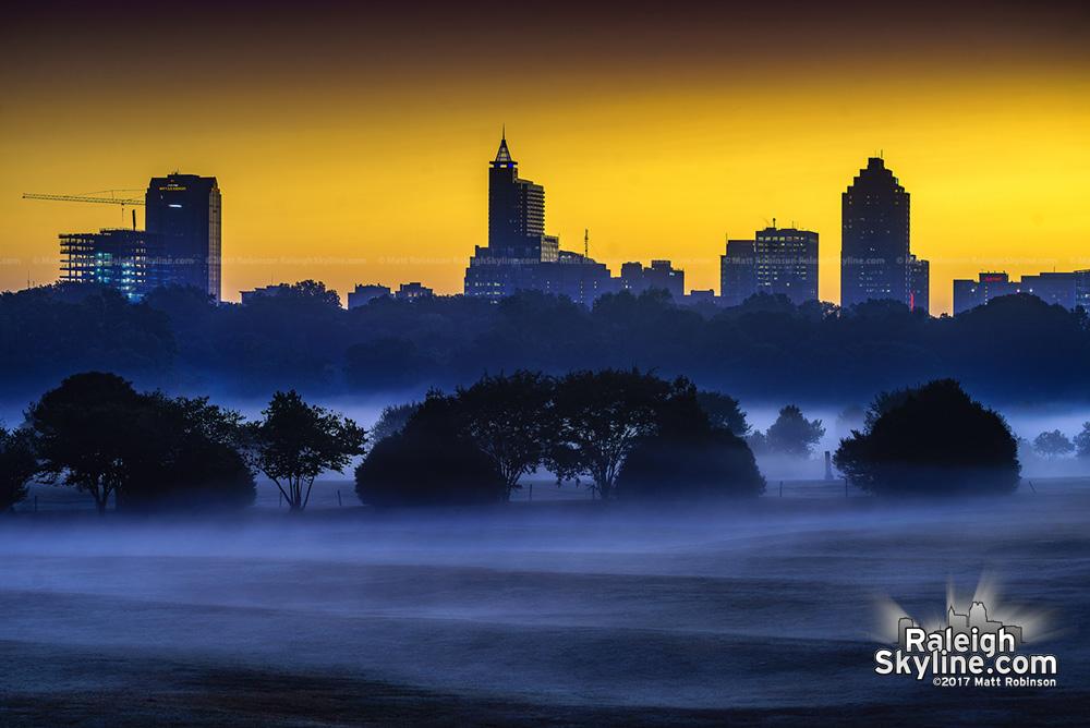 Sunrise colors behind the Raleigh skyline