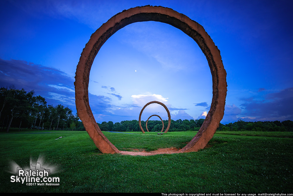 Giant rings at North Carolina Museum of Art with the moon after sunset