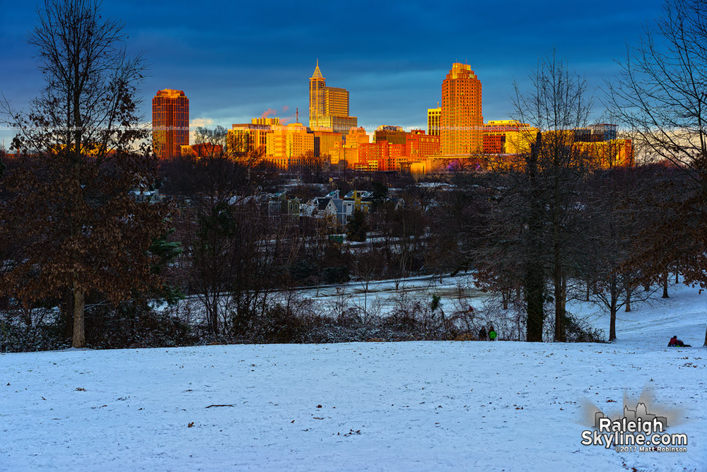 The setting sun illuminates downtown Raleigh in the snow