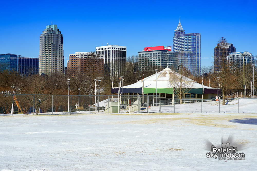 Chavis Park carousel in the snow with the Raleigh Skyline