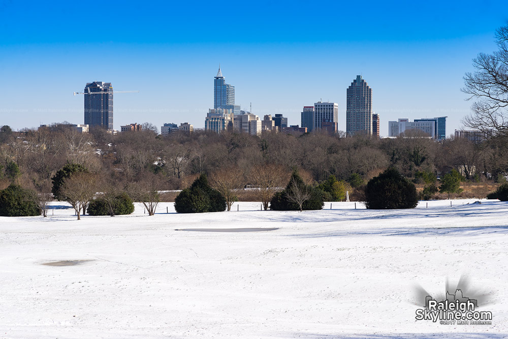 Bright sky and snow with downtown Raleigh