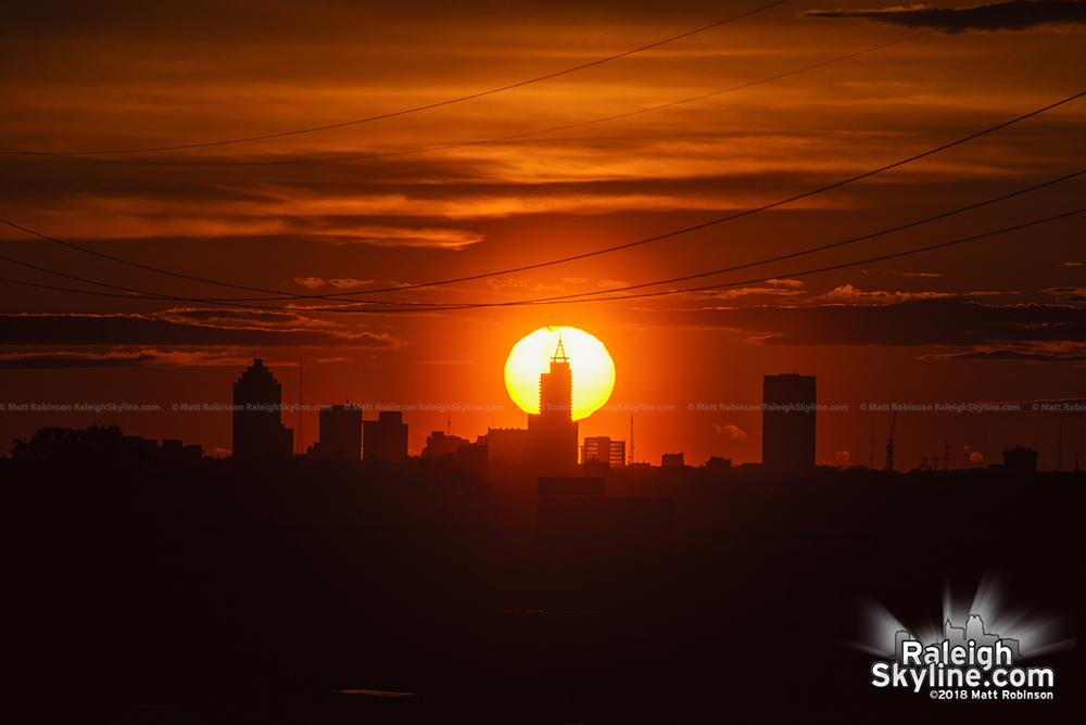Sun sets directly behind Raleigh skyline from Knightdale