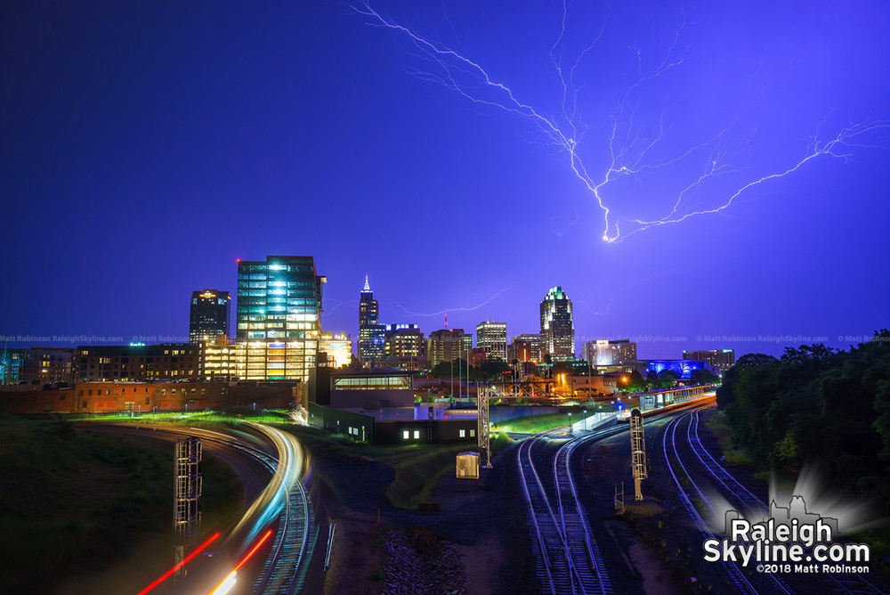 Lightning strikes fill the sky over downtown Raleigh skyline from Boylan Avenue Bridge with train