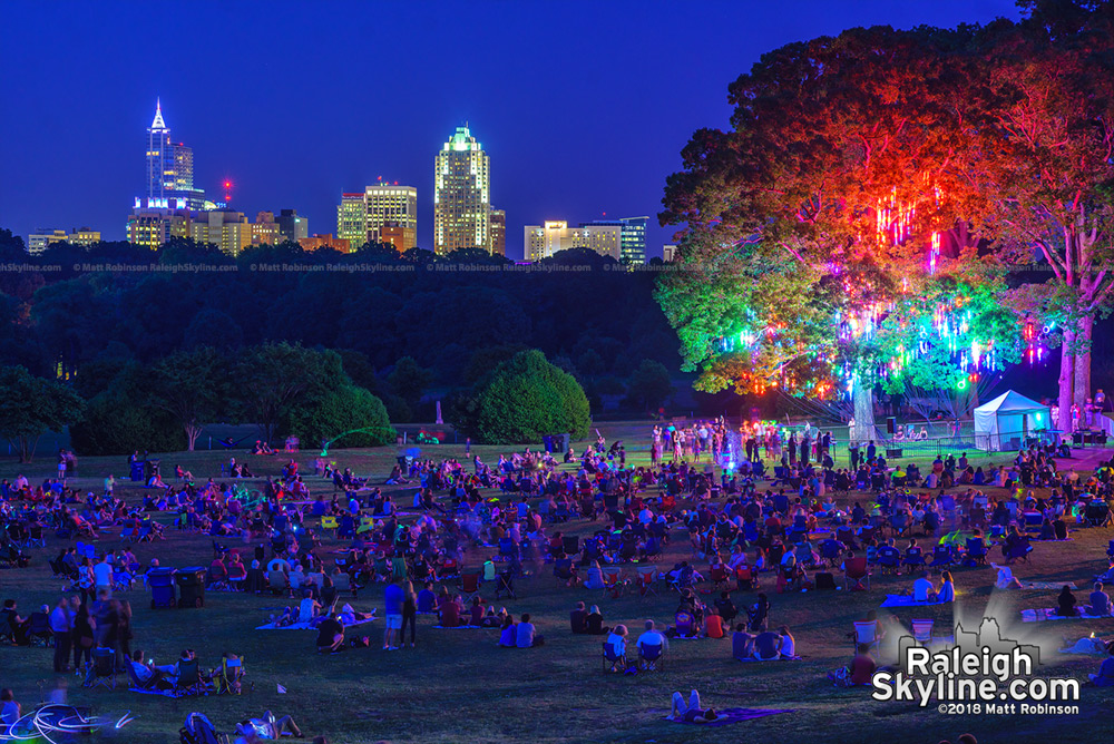 "Downtown Raleigh looms over the crowds gathered to see the ""Light the Woods with Sound"" installation at Dorothea Dix Park"