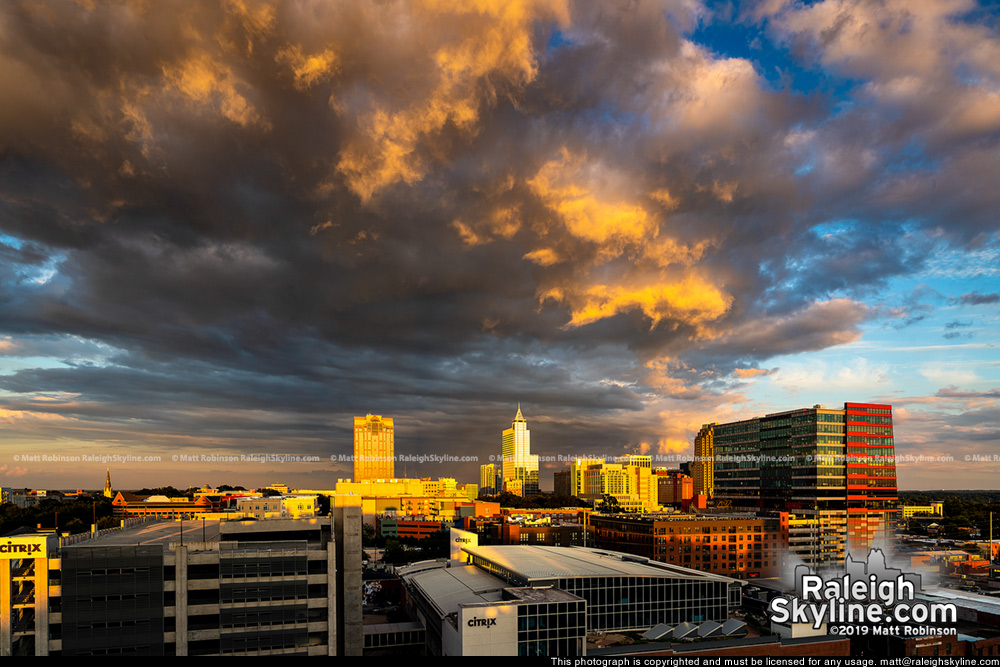 Sunlight underneath clouds with downtown Raleigh