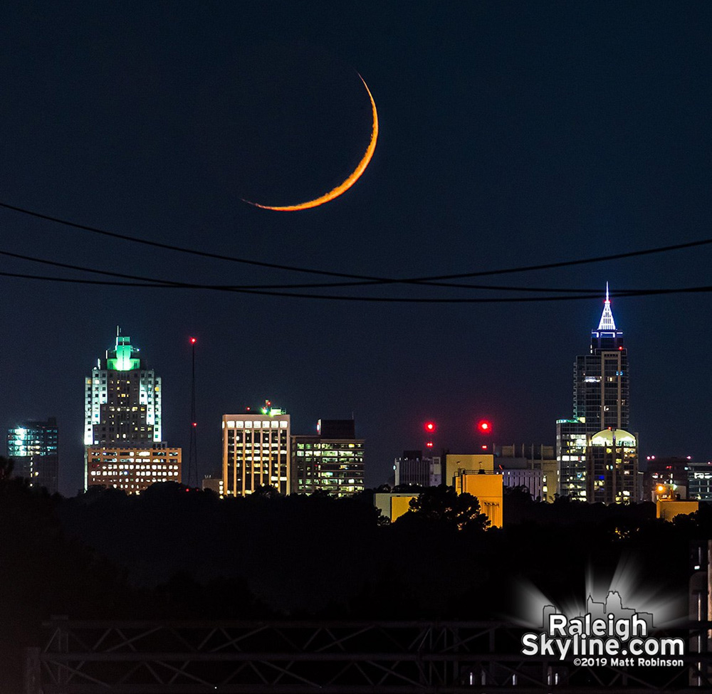 Setting crescent moon aligned behind Raleigh from 7 miles away.  Just 0.8% of the moon is illuminated.