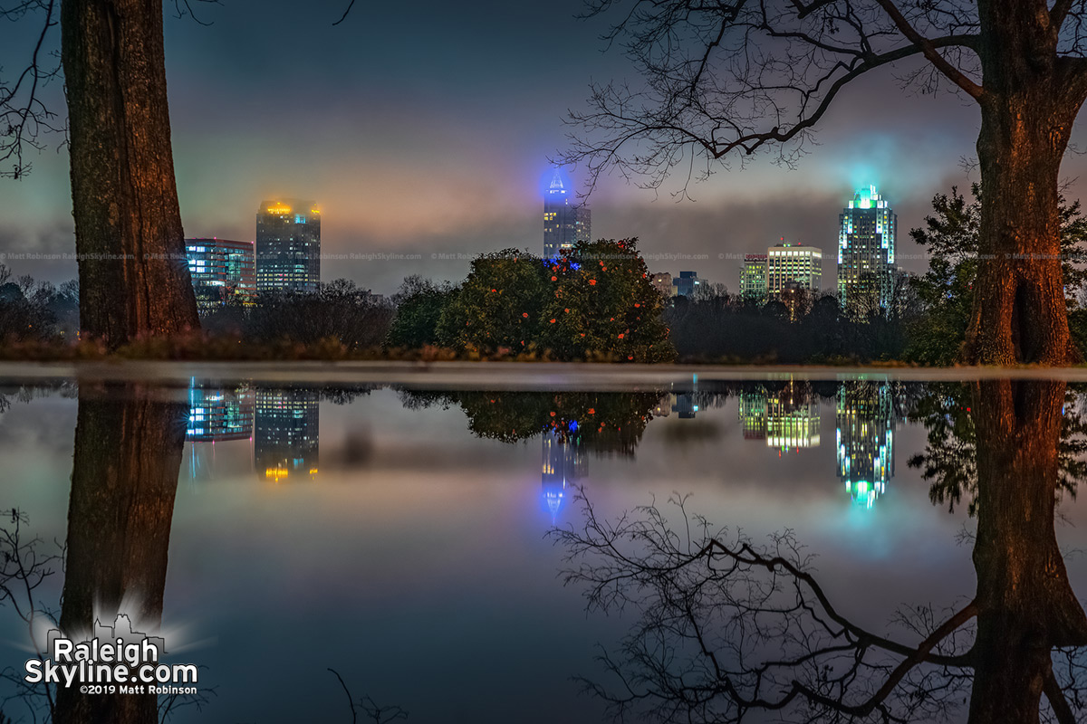 Large puddle reflects the Raleigh skyline at Dix Park