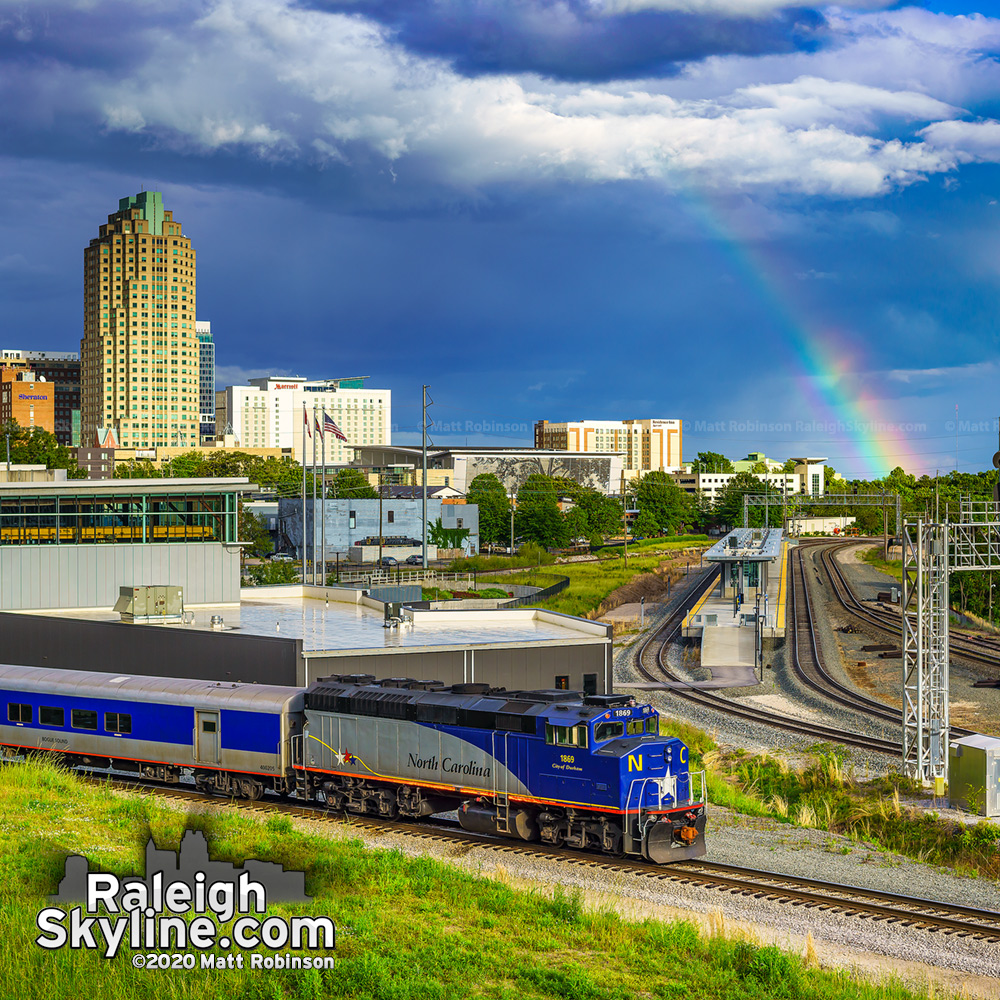 Late day rainbow in downtown Raleigh as the NCDOT City of Durham locomotive heads to the yard.