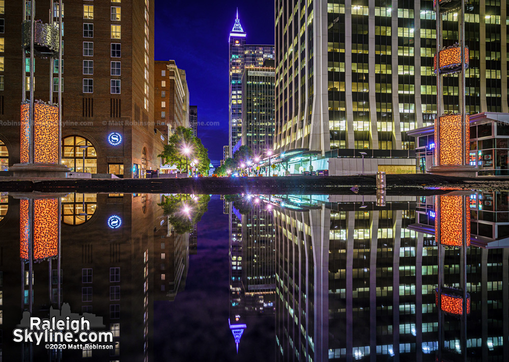 Downtown Raleigh reflecting in a large puddle on Fayetteville Street