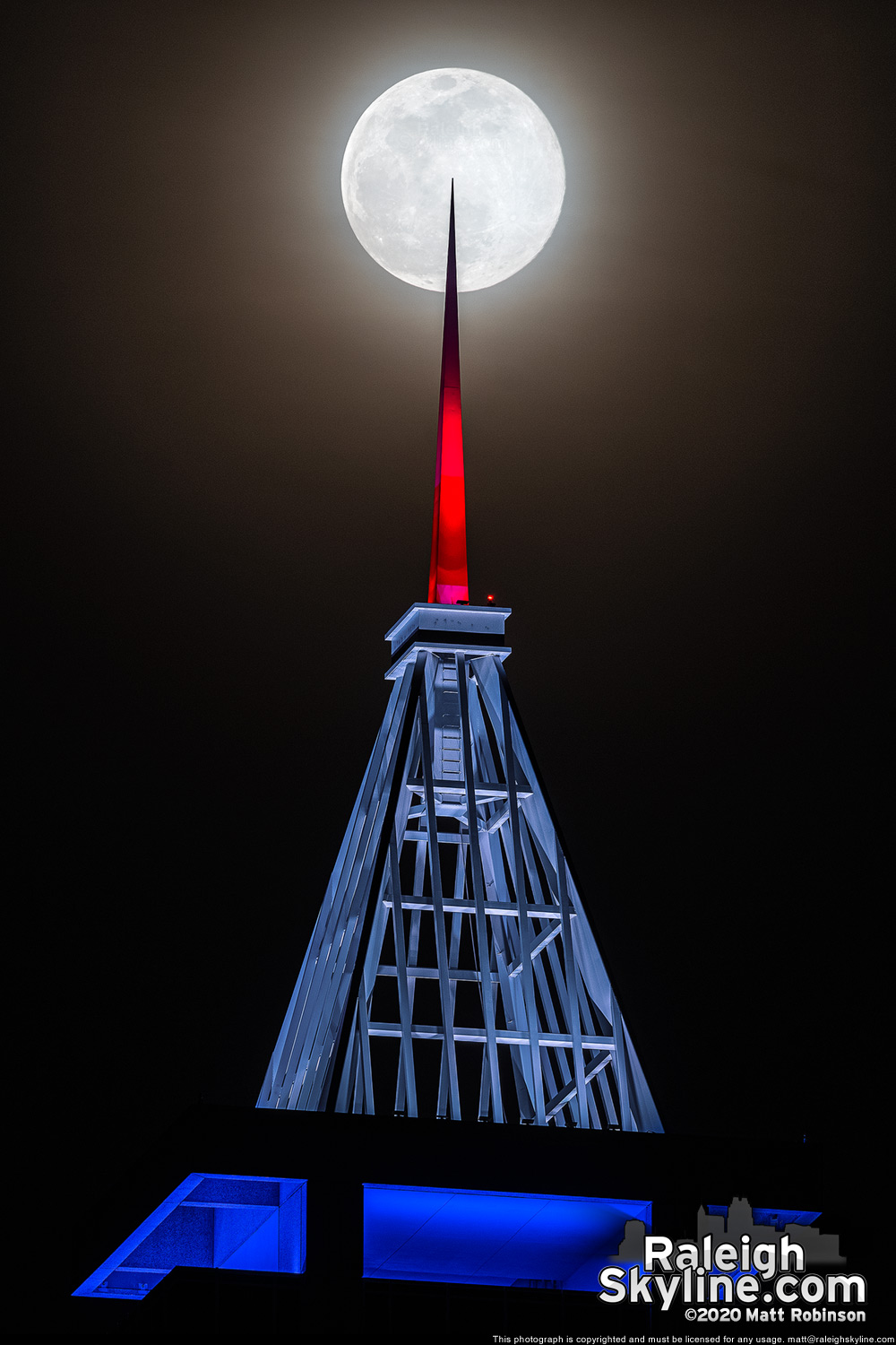 "The ""pink"" supermoon is pierced by the red, white and blue lit spire of PNC Plaza"