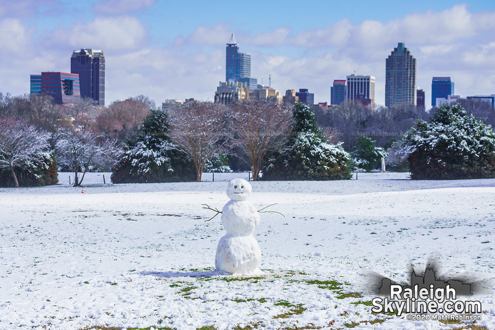 Snowman at Dix Park with downtown Raleigh skyline