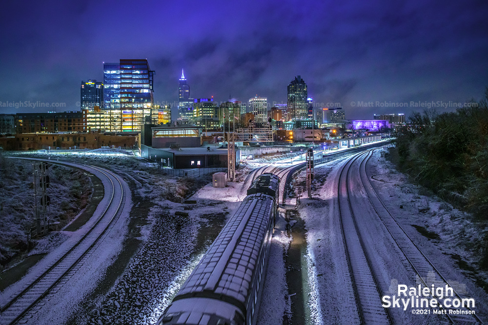 Downtown Raleigh looms as the snow covered 6:30 AM Piedmont Amtrak train pulls into Union Station on January 28, 2021